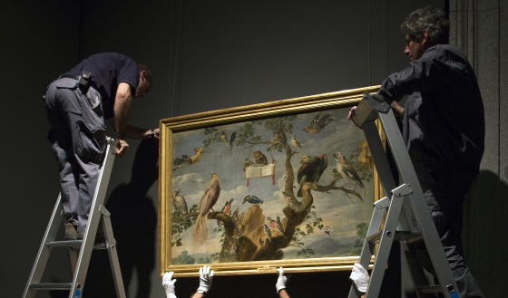 Workers handle a painting at the Prado Museum.