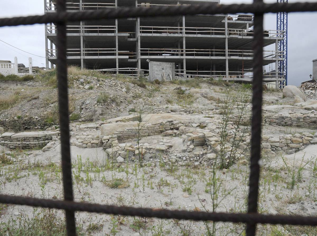 Restos del Castro da Atalaia a los pies del esqueleto sin demoler de la urbanización que paralizaron los vecinos.Foto: El País / XOSÉ MARRA
