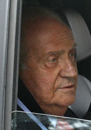 Spain's King Juan Carlos looks on from inside a car as he leaves a Madrid hospital after being discharged.