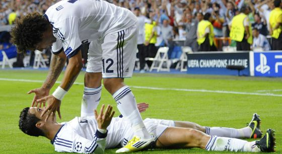 Real Madrid' s Ronaldo celebrates with team mate Marcelo (top) after scoring a goal against Manchester City.