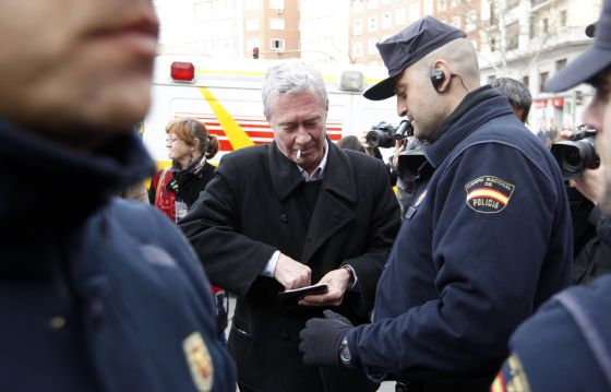 Jorge Verstrynge is asked for his ID card by police officers outside the home of Deputy PM Soraya Sáenz de Santamaría.