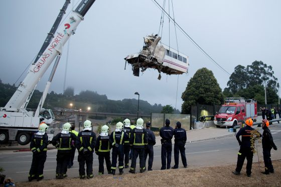 A wagon of a crashed train that killed at least 77 people is lifted at Angrois near Santiago de Compostela, Spain.