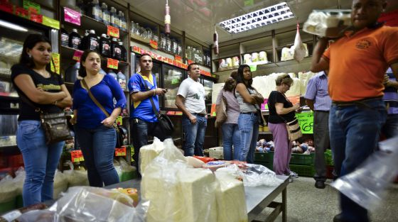 Customers line up to pay for food at a checkout in a Caracas supermarket.