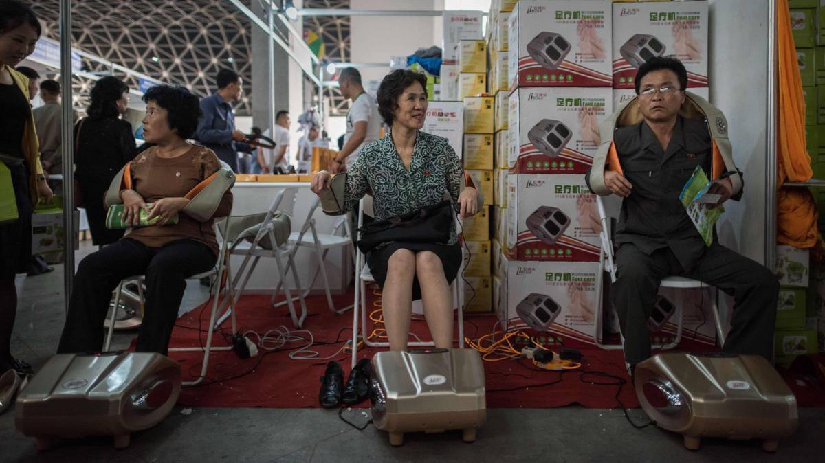 North Korean visitors test massage devices at a Chinese booth at the 13th International Trade Fair in Pyongyang on September 25, 2017.  AFP PHOTO  Ed JONES