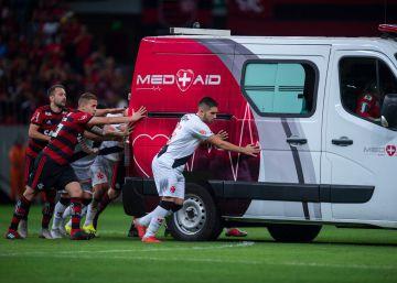 Un grupo de futbolistas empuja una ambulancia para sacarla del campo